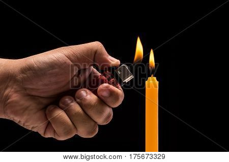 Hand Holding Burning Gas Lighter To Light Candle. Studio Shot Isolated On Black Background