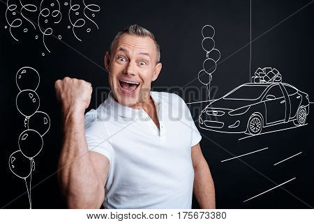 I am the winner. Overjoyed delighted adult man expressing jubilation while feeling happy because of winning a car