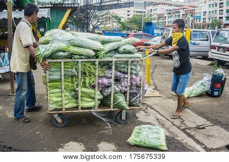 Kota Kinabalu,Sabah-Feb 28,2017:Street vendor with his vegetables ready to sale in market at Kota Kinabalu,Sabah.Street vendors provide local people with fresh & cheap produce in Kota Kinabalu,Sabah,Borneo.
