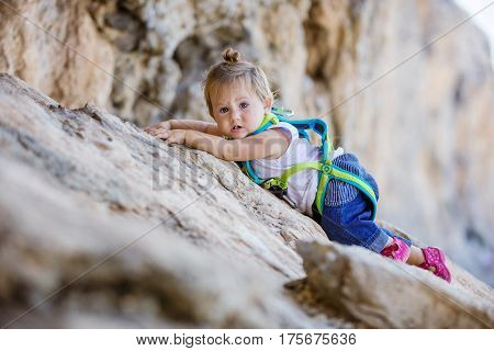 Little girl in safety harness climbing up cliff