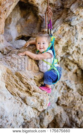 Happy little girl in safety harness climbing on cliff