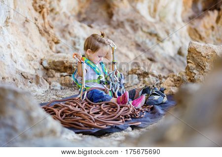 Little girl wearing safety harness and playing with rock climbing gear