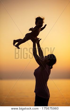 Mother and little daughter having fun on beach at sunset mother throwing girl up in air and catching her