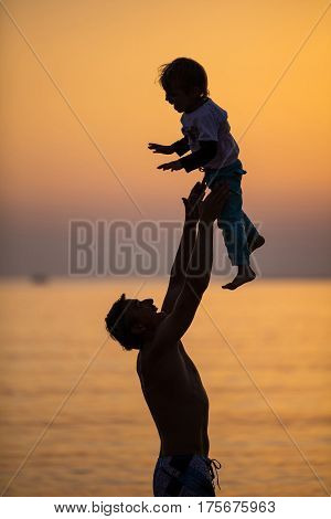 Father and son having fun on beach at sunset father throwing boy up in air and catching him
