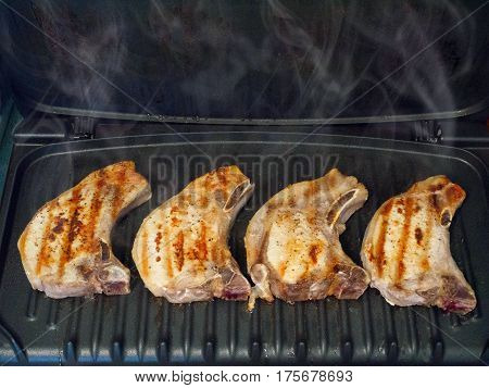 Four pork chops grilled on indoor grill