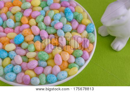 Close up of jelly beans in a on a white cake plate on a green fabric background, with a white bunny looking on