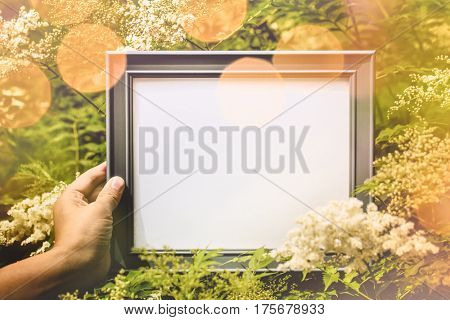 Hand holding picture frame in flower field