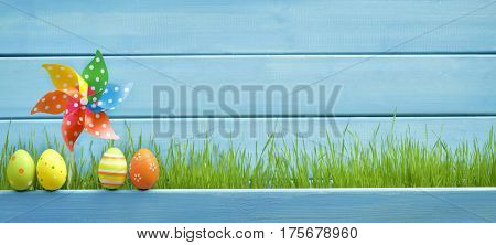 Easter egg,pinwheel and green grass on wooden background
