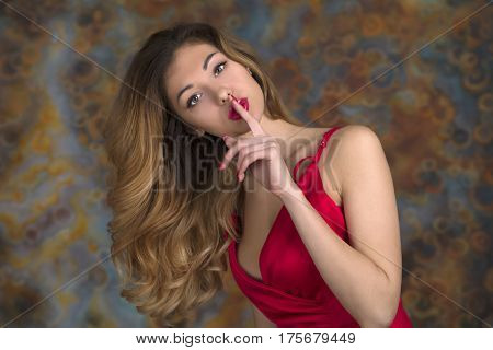 Young beautiful blonde woman in red dress has put forefinger to lips as sign of silence, studio wall background
