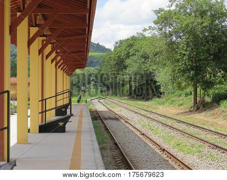 Estação de linha ferrea, vazia, e tranquilo em dia de sol, aguardando a chegada do próximo trem