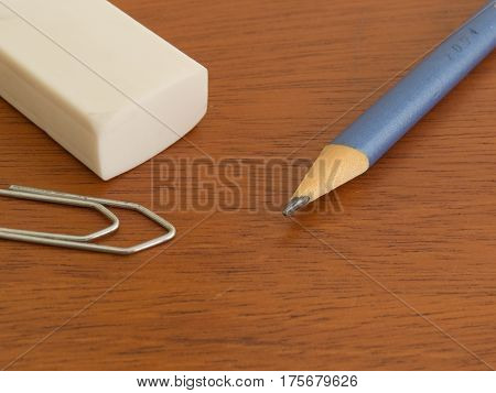 Lápis, borracha e clip sobre mesa de madeira, materiais escolares
