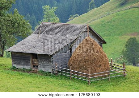Haystack and fance over vintage wooden barn on farm