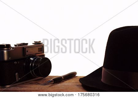 the hat and retro photo camera on white background. The Journey road accesories.Ball point pen ,wooden table