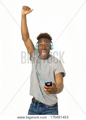 young attractive black student man with headphones and mobile phone listening to music dancing and singing the song happy and excited having fun isolated on white background