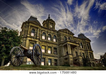 Cadiz Ohio USA- July 5 2016: The Harrison County Courthouse standing in the background with a period Civil War canon displayed in the foreground.