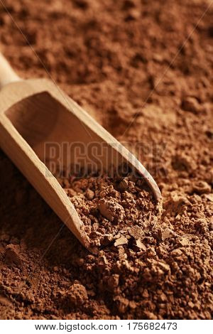 Wooden scoop on cocoa powder background