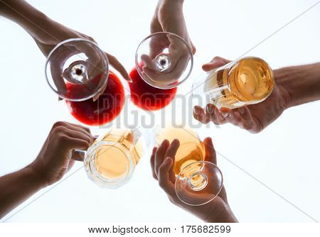 Friends clinking glasses with drinks, below view
