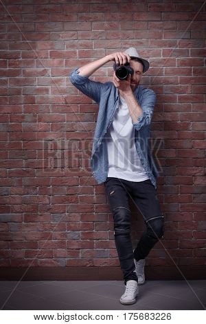 Handsome photographer near brick wall