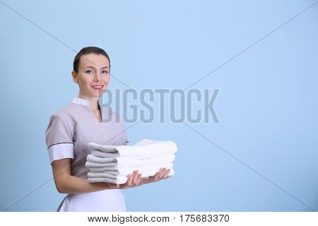 Attractive chambermaid holding pile of clean towels on color background