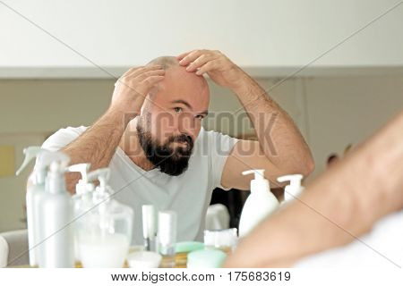 Adult man with hair loss problem looking in mirror at home