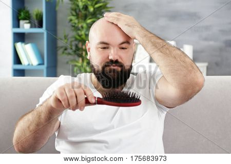 Bald adult man with hair brush  at home
