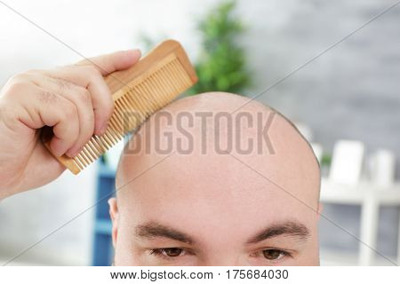 Bald adult man with comb on blurred background, closeup