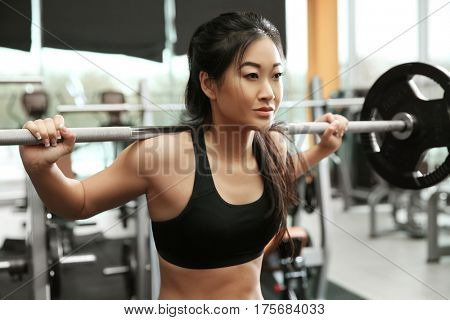 Young sporty woman training with barbell at gym