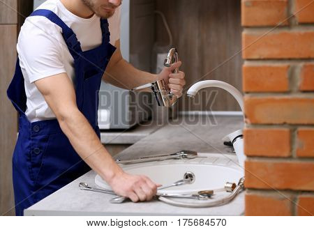 Young plumber replacing faucet in kitchen