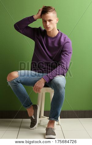 Handsome young man sitting on stool near color wall