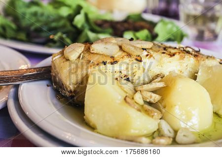Portuguese style Bacalhau fish with garlic on a plate