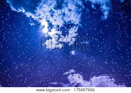 Amazing blue dark night sky with many stars bright full moon and cloudy. Outdoor at nighttime with moonlight. Vivid colors. Pretty nature use as background.