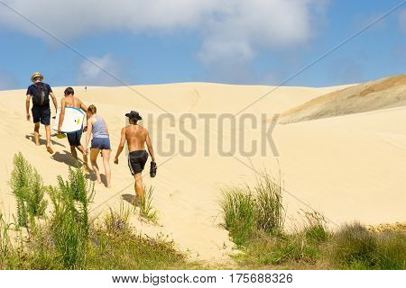 Te Paki, New Zealand - February 14,2017;Young people head off climbing Te Paki Sand Dunes enormous white dunes a favorite tourist attraction and fun place Northland New Zealand