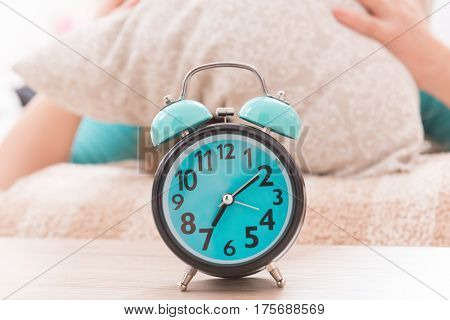 Alarm clock and woman with pillow on her head in the background
