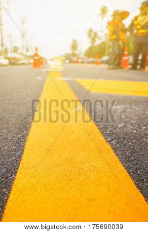 Worker operating asphalt paver and making line during road construction and repairing works