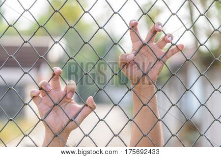 Hand holding on Metal Grille (Blur background)