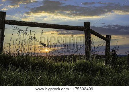 Setting sun as seen through a brace for a high tensile wire fence in rural Ohio