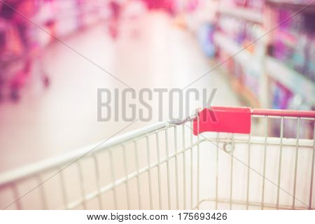 Blurred Background: Close Up Shopping Cart In Supermarket Store With Bokeh Light Background