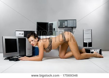 Sensual woman crowling with computers stacked on background