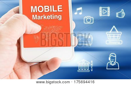 Hand Holding Mobile Phone With Mobile Marketing Word With Related Icon On Motion Blue Blur Backgroun