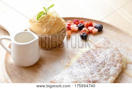 Fresh Dessert Soft Vanila Roti With Ice Cream ,syrup ,strawberry And Blueberry On Plate In Restauran