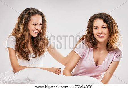 Two cheerful women having fun in bed on weekend