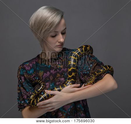 Young woman holding snake on gray background