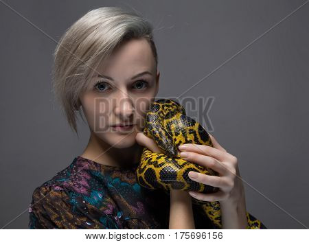 Blond woman holding anaconda on gray background