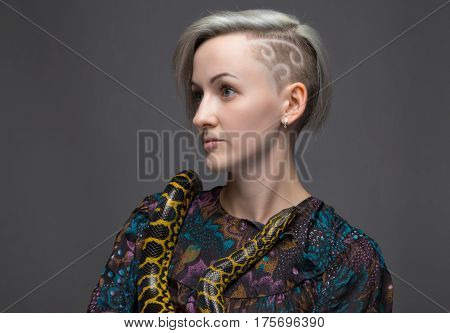 Shaved woman and yellow anaconda on gray background