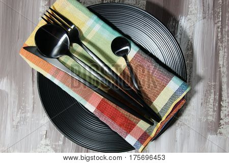A black plate with fork spoon knife cutlery on a napkin top view.