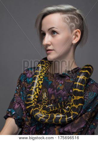 Young woman and yellow reptile on gray background
