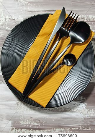 A black plate with fork spoon knife cutlery on a mustard colored napkin top view.
