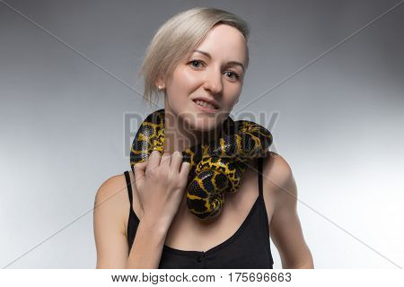 Blond woman and strangling snake on gray background