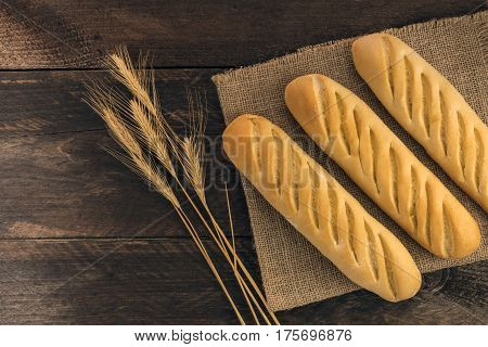 An overhead photo of freshly baked loaves of white bread with wheat spikes, on a rustic background with a place for text