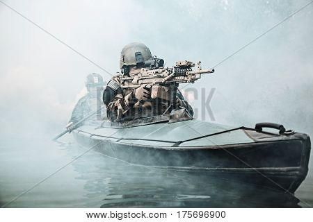 Special forces marine operators in camouflage uniforms paddling army kayak through river fog. Diversionary mission, machine gunner ahead